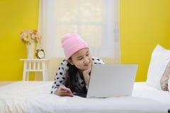 Giovane bello adolescente sorridente che per mezzo del computer portatile Immagini Stock Libere da Diritti