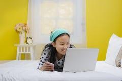 Giovane bello adolescente sorridente che per mezzo del computer portatile Immagini Stock