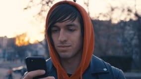 Giovane bello al fondo urbano della via soleggiata della città Tipo in maglia con cappuccio rossa facendo uso dello smartphone,  video d archivio