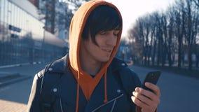 Giovane bello al fondo urbano della via soleggiata della città Tipo in maglia con cappuccio rossa facendo uso dello smartphone,  archivi video