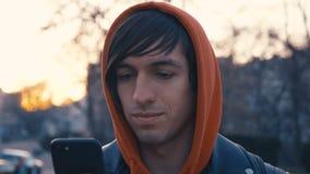 Giovane bello al fondo urbano della via soleggiata della città Tipo in maglia con cappuccio rossa facendo uso dello smartphone,  stock footage