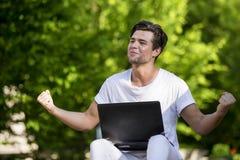 Giovane bello allegro felice con un computer portatile Immagini Stock Libere da Diritti