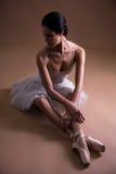Giovane bello ballerino di balletto della donna nella seduta del tutu immagine stock libera da diritti