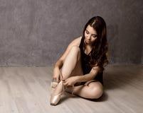 Giovane bello ballerino di balletto in scarpe del pointe, ballanti in un fondo grigio Immagine Stock