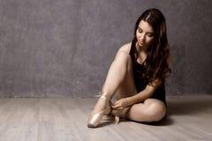 Giovane bello ballerino di balletto in scarpe del pointe, ballanti in un fondo grigio Fotografie Stock