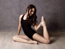 Giovane bello ballerino di balletto in scarpe del pointe, ballanti in un fondo grigio Fotografie Stock Libere da Diritti