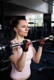 Giovane bello bicipite di addestramento della donna con il bilanciere Fotografie Stock