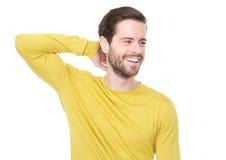 Giovane bello in camicia gialla che sorride con la mano in capelli fotografia stock