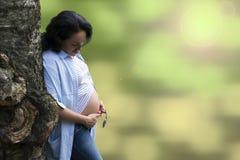 Giovane bello castana dai capelli lunghi appoggiandosi un albero bizzarro ed esaminando la sua pancia incinta fotografia stock libera da diritti