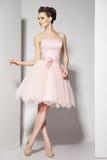 Giovane bello castana in vestito rosa su bianco immagine stock