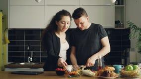 Giovane bello caucasian che la donna di affari abbastanza riccia è venuto a casa da lavoro, il suo marito bello è cucinare, tagli stock footage