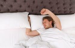 Giovane bello che allunga mentre trovandosi sotto la coperta bedtime fotografia stock