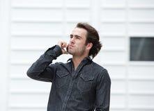 Giovane bello che comunica sul telefono mobile Immagine Stock