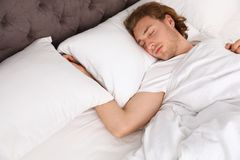 Giovane bello che dorme sul cuscino bedtime fotografia stock