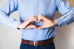 Giovane bello che fa forma con le dita delle mani, amore, relazione, datazione del cuore fotografie stock