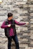 Giovane bello che indossa la pistola a acqua ad alta pressione della tenuta rossa quadrata del modello, indicante verso il muro d Fotografia Stock Libera da Diritti