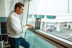 Giovane bello che lavora con il computer portatile in aeroporto quando aspettano il suo aereo immagini stock libere da diritti