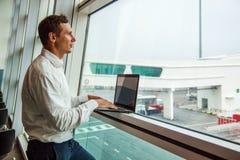 Giovane bello che lavora con il computer portatile in aeroporto quando aspettano il suo aereo fotografie stock
