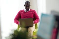 Giovane bello che lavora con il suo computer portatile a casa Fotografia Stock
