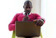 Giovane bello che lavora con il suo computer portatile a casa Fotografie Stock Libere da Diritti