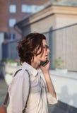 Giovane bello che parla sullo smartphone davanti a costruzione moderna Immagine Stock Libera da Diritti
