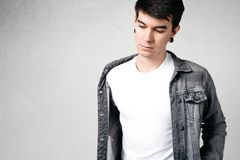 Giovane bello che porta maglietta e rivestimento in bianco, fondo bianco della parete di mattoni fotografie stock libere da diritti