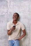 Giovane bello che ride con il telefono cellulare Fotografie Stock Libere da Diritti