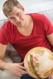 Giovane bello che si siede a casa con il globo Fotografia Stock