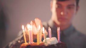 Giovane bello che si siede davanti a poche candele di illuminazione del dolce con l'accendino Il tipo solo ha festa di compleanno video d archivio