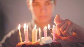 Giovane bello che si siede davanti a poche candele di illuminazione del dolce con l'accendino Il tipo solo ha festa di compleanno archivi video