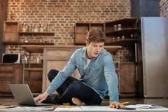 Giovane bello che si siede sul pavimento e che lavora al progetto Immagini Stock