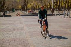 Giovane bello che si siede sulla bici e che smilling nella città fotografia stock
