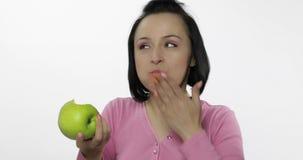 Giovane bello cibo della donna grande e mela verde succosa su fondo bianco archivi video