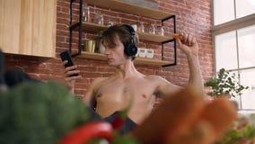 Giovane bello con il torso nudo che mangia carota e musica d'ascolto sullo Smart Phone mentre sedendosi nella cucina Dieta archivi video