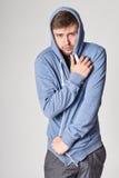 Giovane bello con la barba leggera in maglia con cappuccio blu, sul BAC grigio Immagine Stock Libera da Diritti