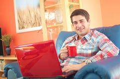 Giovane bello con la tazza di caffè e del computer portatile Fotografia Stock