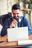 Giovane bello con le cuffie facendo uso del computer portatile in caffetteria Immagini Stock Libere da Diritti