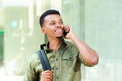 Giovane bello con lo zaino che parla sul telefono cellulare Immagine Stock