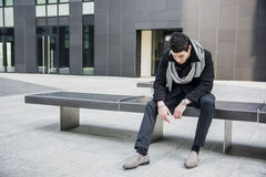 Giovane bello d'avanguardia che si siede sul banco di pietra Fotografie Stock