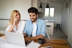 Giovane bello e donna attraente che lavorano al computer portatile Immagine Stock Libera da Diritti