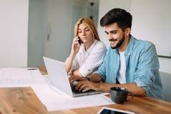 Giovane bello e donna attraente che lavorano al computer portatile Immagine Stock