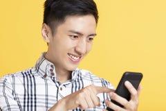 Giovane bello facendo uso dello Smart Phone fotografia stock libera da diritti