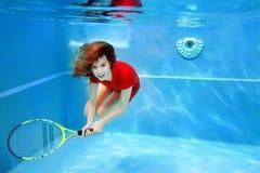 Giovane bello giocar a tennise della ragazza subacqueo nella piscina fotografia stock libera da diritti