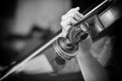 Giovane bello giocatore del violino della donna che esamina macchina fotografica sopra lo strumento sul suo arco della tenuta del fotografie stock