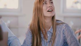 Giovane bello impiegato corporativo femminile positivo della società che ascolta il capo femminile, sorridente alla riunione con archivi video