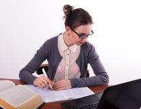 Giovane bello insegnante femminile che si siede ad una tavola Fotografia Stock
