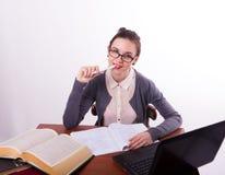 Giovane bello insegnante femminile che si siede ad una tavola Immagini Stock