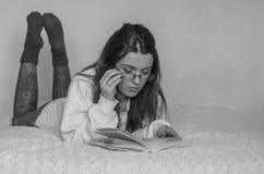 Giovane bello insegnante in vetri con capelli lunghi che legge un libro che si trova sul letto Immagine Stock