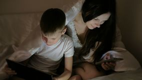 Giovane bello Internet di lettura rapida della mamma della donna in suo telefono mentre il suo fumetto di sorveglianza del figlio video d archivio