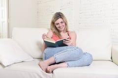 Giovane bello libro di lettura caucasico della donna che studia menzogne comoda sul sofà domestico che sembra felice immagine stock libera da diritti